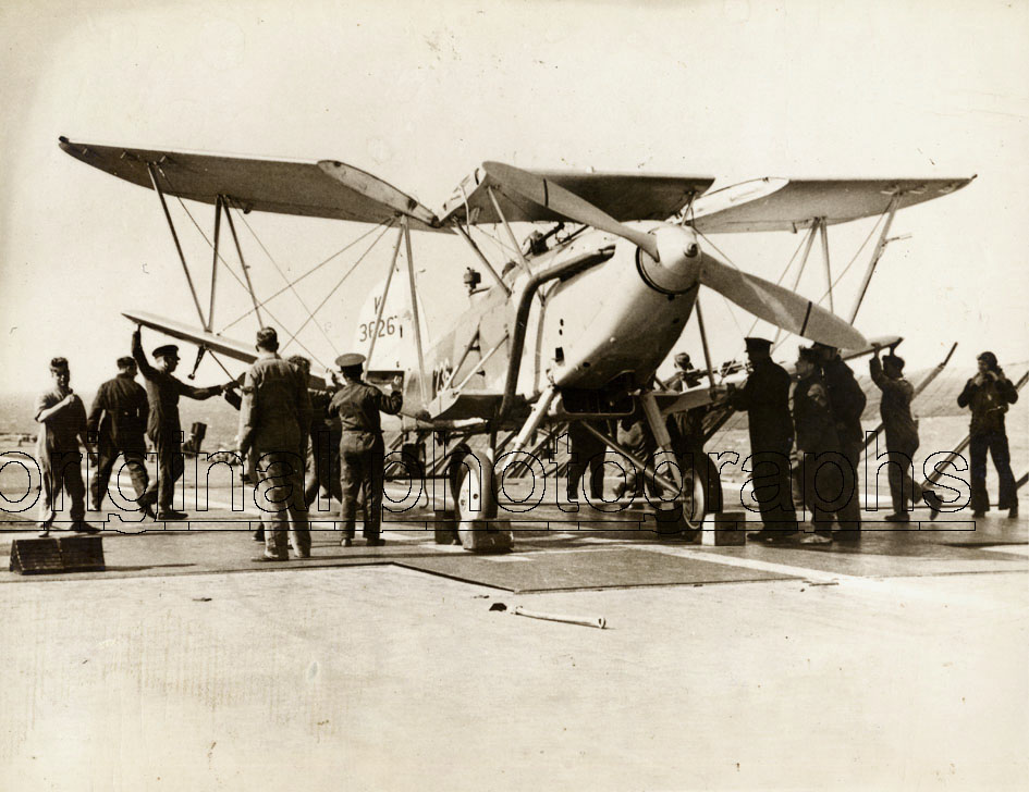 HMS FURIOUS. - Mechanics on the plane-carrier HMS Furious, folding the wings of a Hawker Osprey, K3626, before lowing into the hangar.